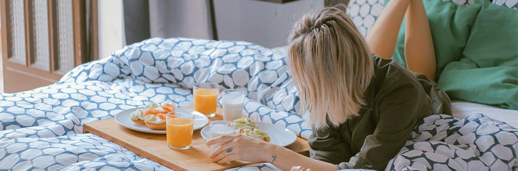 Bild som illustrerar en hotellgäst med frukostbricka